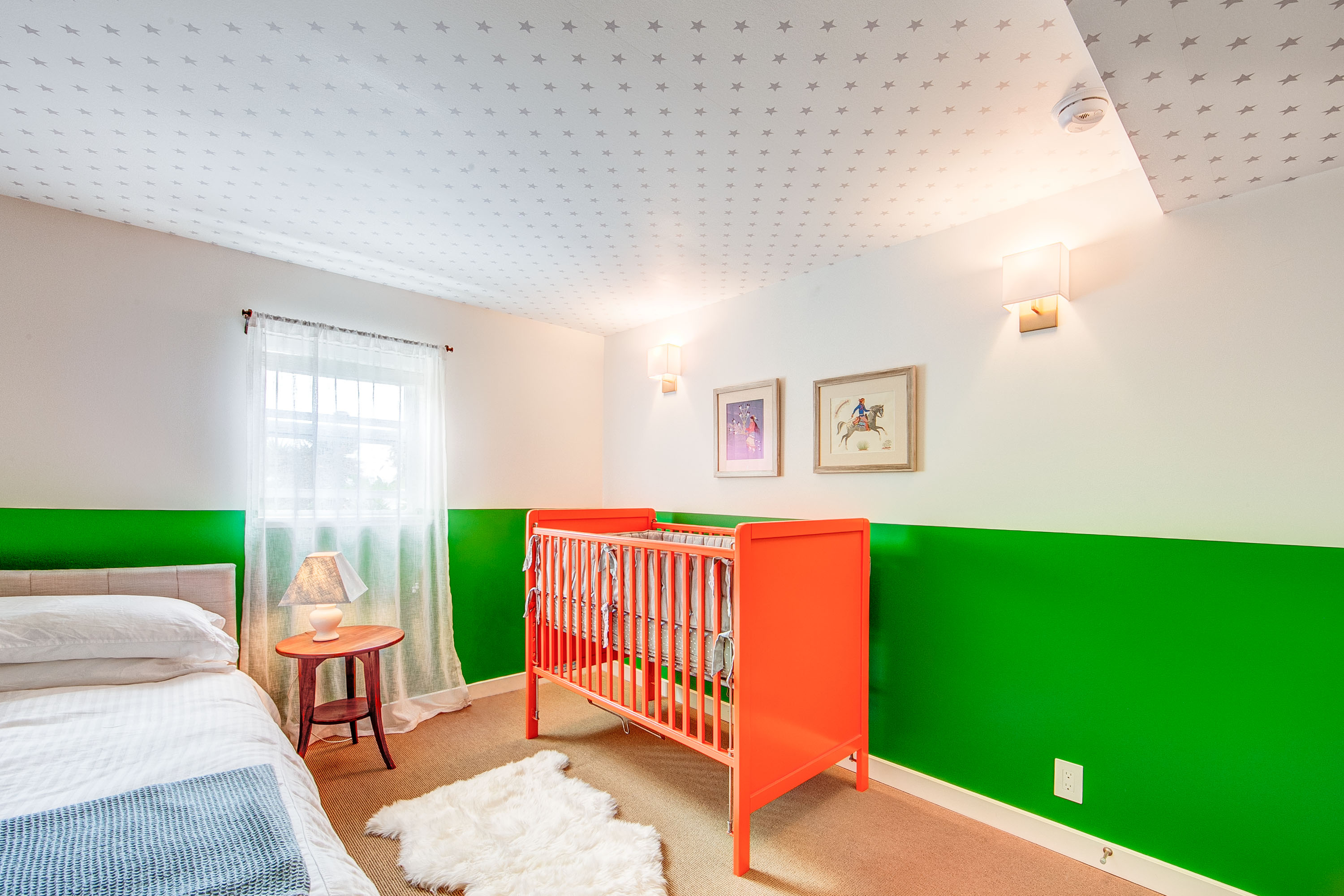 Bright nursery with wallpapered ceiling and painted wainscoting