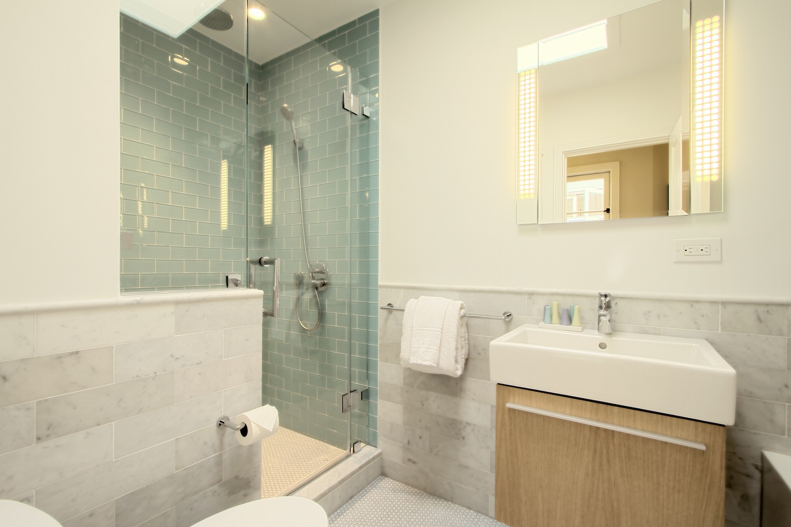 Marble bath showcased with glass tile shower enclosure